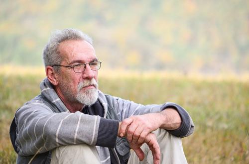 Elderly man sat outside in a meadow